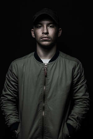 teen boy posing with black cap and bomber jacket in front of black background
