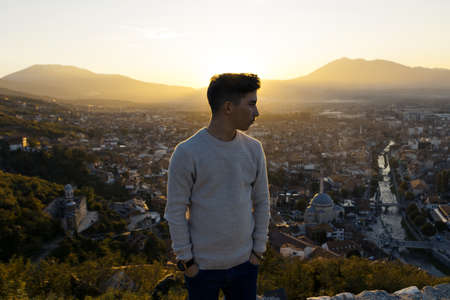 serious teen looking sideways to the city of Prizren, Kosovo in the evening sunshine