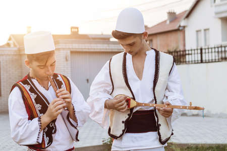 teen boys in traditional albanian costume playing music with flute and string instrument in the evening sunlight Stok Fotoğraf