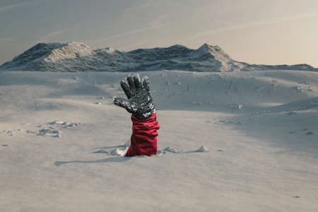 Hiker stretching out his snow covered hand to signal help because of snow avalanche . Danger extreme concept