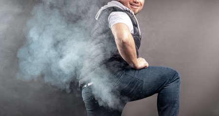 Mann hebt das Bein und furzt vor grauem Hintergrund