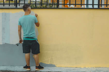 back of teen with brush in the hand standing in front of yellow painted wall