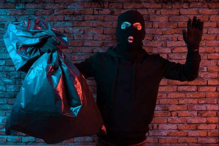 un voleur surpris lève les mains et s'illumine des lumières de la police