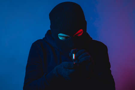 Young man in hoodie and balaclava looking at a cigarette and looking down Stok Fotoğraf