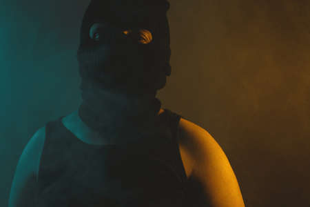 Portrait of relaxed man in black balaclava, illuminated from abstract light in green and yellow colors Banco de Imagens