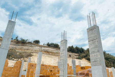 concrete pillars withred brick blocks in front of high cliffs 写真素材 - 130047897