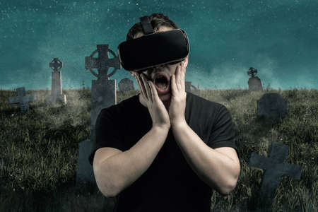 scary young man getting experience with vr device playing horror game in front of spooky graveyard