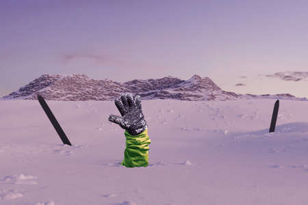 Skier stretching out his snow covered hand next to trekking poles to signal help because of snow avalanche . Danger extreme concept