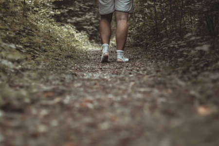 male feet walking with torn socks through a green forest