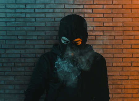 young man in hoodie and balaclava in front of brick wall looking down and blow smoke out Reklamní fotografie