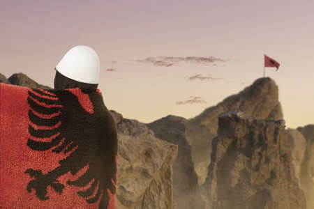 side view of man covered with fluffy albanian flag in front of blurred mountains to celebrate. Concept celebrate the national holiday of november 28th