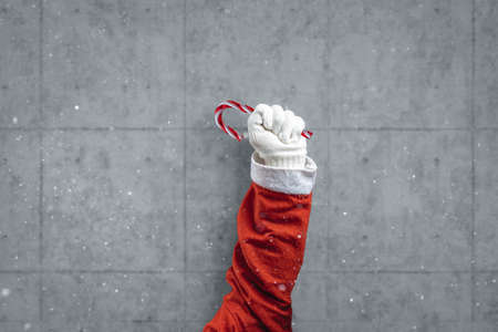 arm of santa claus raised up and holding a candy cane in front of concrete wall Reklamní fotografie