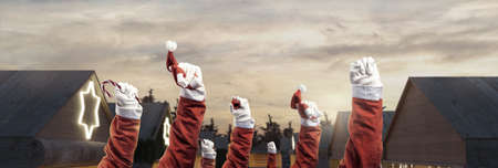 left fists of santa clauses raising up to protest in front of wooden huts of christmas market