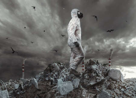 survivor with white overall and gas mask reach the top of garbage dump and watching to the apocalyptic sky Stock Photo