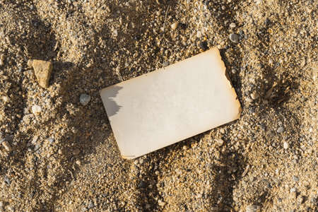top view of an open empty page laying on sand