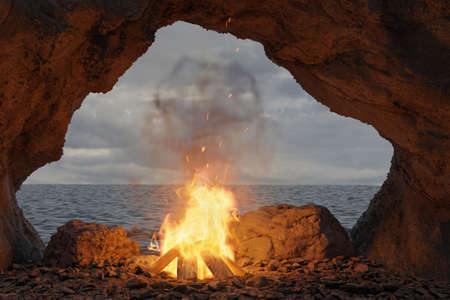 3d rendering of big bonfire with sparks and particles in front of sea and cave
