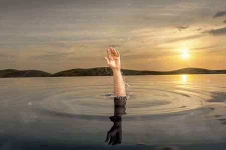 Swimmer stretching out his wet hand from water to signal help. Danger extreme concept