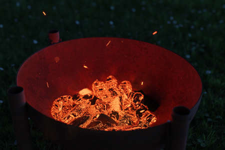 3d rendering of rusty fire bowl grill filled with glowing charcoals at night Stock fotó