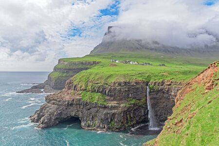 The iconic waterfall of Gasadalur on faroe islands and the remote village in the background Imagens