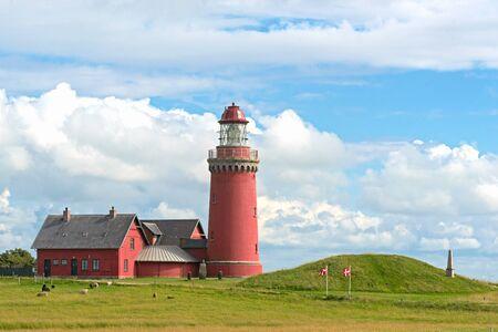 The red Lighthouse Bovbjerg Fyr with green grass and blue sky, Jutland, Denmark