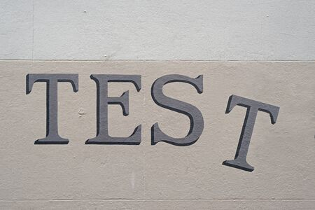 The word TEST painted in a serif handwriting type on a wall