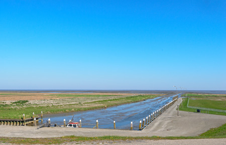 The very small tidal sea harbor of Noordpolderzijl at the Wadden Sea. At the moment of this photo there is hardly any water due to low tide. Stock Photo