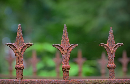 Detail of an old rusty fence with three fleur-de-lis Stock Photo