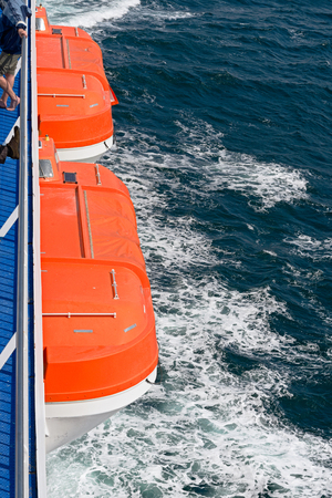 Two orange life boats on a ferry on sea Imagens