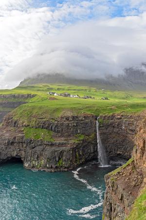 フェロー諸島とバック グラウンドでリモートの村 Gasadalur の象徴的な滝