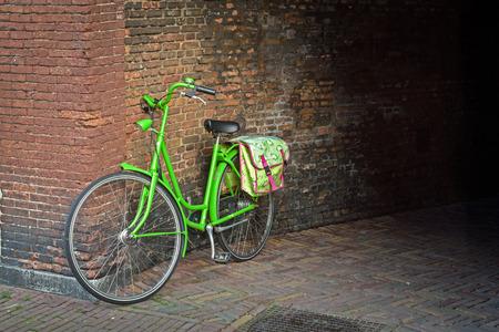 壁の前にサイクル バッグ緑の伝統的なオランダ自転車駐車