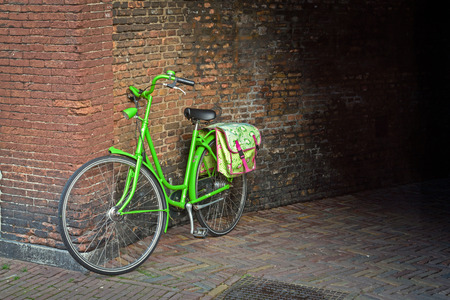 Traditional dutch green bicycle with cycle bag parked in front of a wall