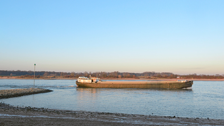 nederland: Cargo transport by ship at Dutch river the Waal near Beuningen in the evening sun Stock Photo