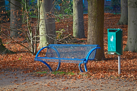 Blue park bench with a green trash can in autumn Imagens