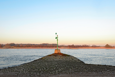 Green beacon in the river Waal in the evening sun