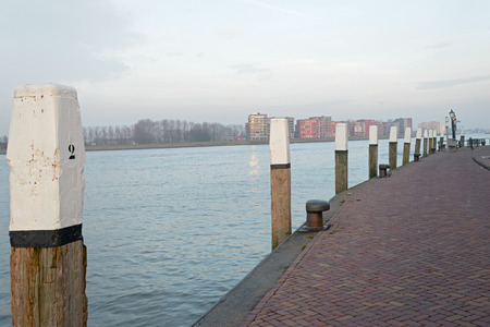 Quay along the Niewe Merwede with woorden bollard poles with white top in Dordrecht, the Netherlands