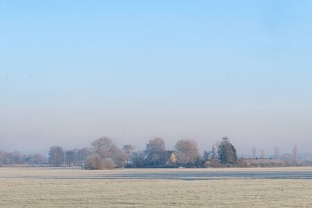 Dutch rural winter landscape with frozen meadow and a farm