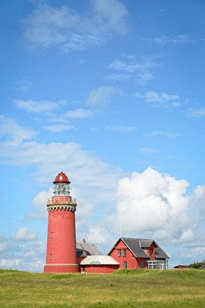 Red Lighthouse Bovbjerg Fyr with green grass and blue sky