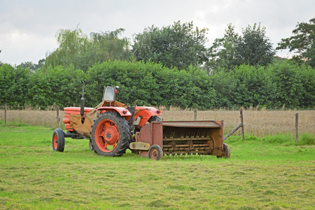Old abandoned tractor with rusty hay turner in meadow Imagens