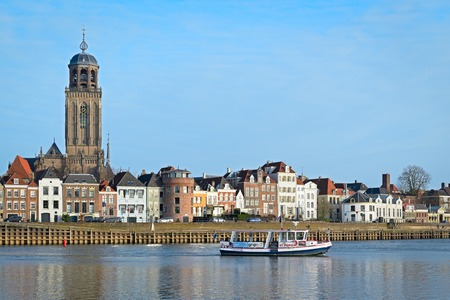 ijssel: DEVENTER, THE NETHERLANDS - DECEMBER 24, 2016: Ferry is crossing the river IJssel with a view of the medieval city