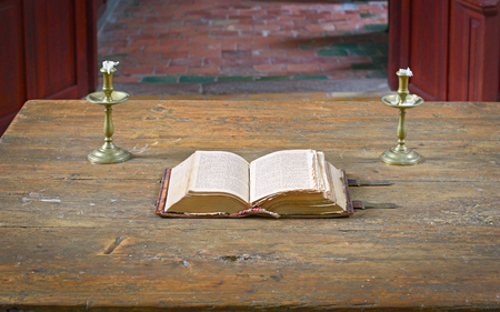 Very old open bible on table in medieval church