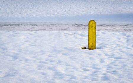 冬の間に雪の中で 1 つの黄色いポール 写真素材