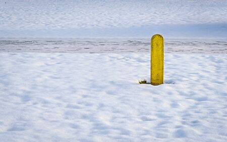 One yellow pole in the snow during winter