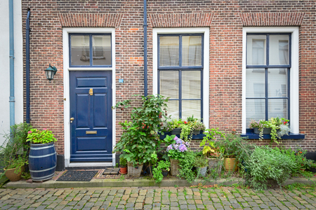 냄비에 꽃과 오래 된 네덜란드 하우스의 벽돌 외관
