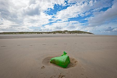 フリーラントのオランダのビーチに緑のプラスチックこみ