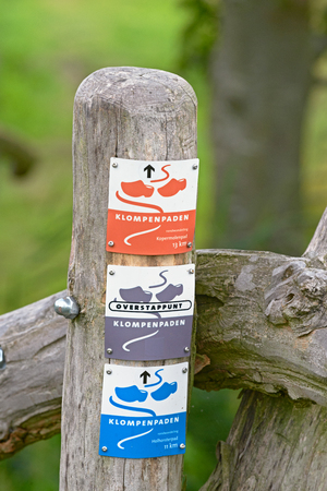 APELDOORN, THE NETHERLANDS, AUGUST 3, 2016 - Direction signs are affixed on a pole marking the hiking trails in rural areas in Gelderland. These trails are called Klompenpaden - Wooden clogs trails.