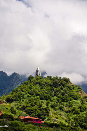 Wide view over the unique mountainous landscape of Madeira, with church on a hill in the clouds, Sao Vincente, Madeira, Portugal, Europe