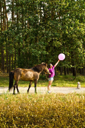 A woman in a magenta T-shirt walks with a brown pony and a small dog, stretches and reaches for a pink balloon