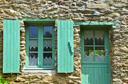 Sunny view of a window with green shutters and a house wall made of natural stone, in which a crocheted, white curtain hangs Reklamní fotografie