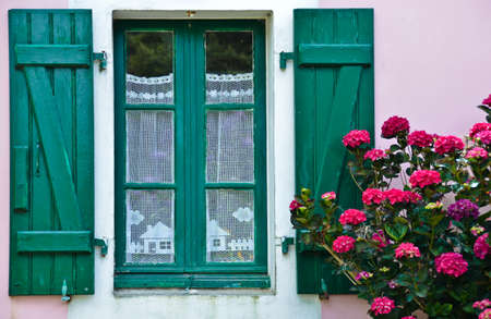 Sunny view of a window with green shutters and a pink house wall, in which a crocheted, white curtain hangs