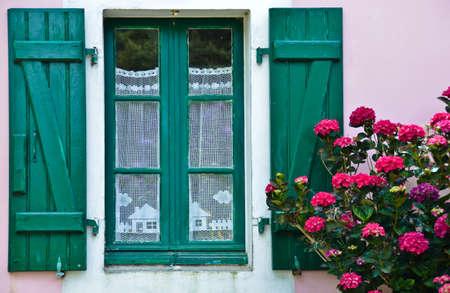 Vue ensoleillée d'une fenêtre aux volets verts et d'un mur de maison rose, dans lequel est suspendu un rideau blanc au crochet